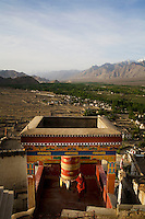 A monk spins the prayer wheel before morning prayers at sunrise at Thiksay Monastery on 1st June 2009. Thiksay, founded in the 15th century, sits on a hill 19 km southeast of Leh town, and houses approximately 100 monks. Leh, seen in the background, is tucked away at 3505m in the Indian Himalayas, Jammu and Kashmir state, India. Photo by Suzanne Lee / For The National