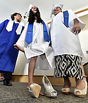 Destiny Arroyo of Manchester, rubs her foot finding her new shoes a little uncomfortable while waiting for the march to start with fellow students,   prior to the Great Path High School graduation ceremony, Wednesday, June 8, 2016, at Manchester Community College.At right is Darnisha Antuna of New Britain.  (Jim Michaud / Journal Inquirer)