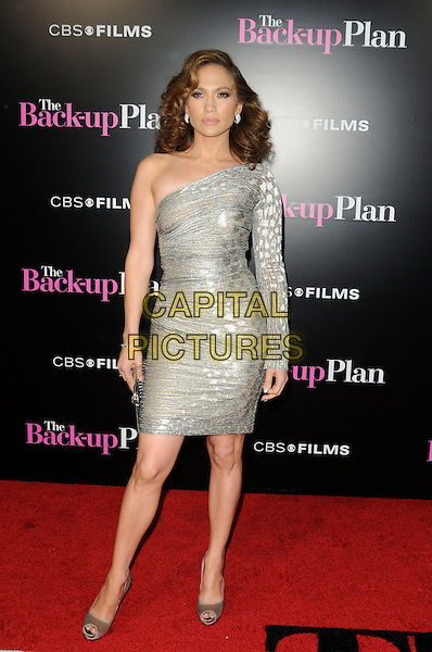 "JENNIFER LOPEZ .arriving at the premiere of CBS Films' ""The Back-up Plan"" at the Regency Village Theatre in Westwood, California, USA, April 21st, 2010..arrivals full length silver one shoulder sleeve shiny sheer shimmery dress peep toe heels silk satin beige gold  hand on hip clutch bag .CAP/ROT.©Lee Roth/Capital Pictures"