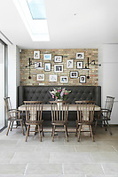 A family dining area in the kitchen with a leather upholstered banquette windsor chairs
