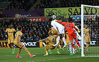 Leroy Fer of Swansea City is challenged by Ben Davies and Michel Vorm of Tottenham Hotspur as he rises to head the ball during the Premier League match between Swansea City and Tottenham Hotspur at The Liberty Stadium, Swansea, Wales, UK. Wednesday 05 April 2017