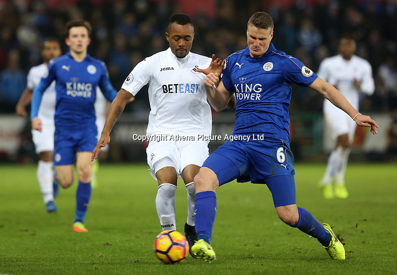 Jordan Ayew of Swansea City is challenged by Robert Huth of Leicester City during the Premier League match between Swansea City and Leicester City at The Liberty Stadium, Swansea, Wales, UK. Sunday 12 February 2017