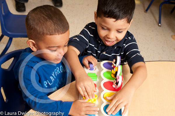 Education preschool first days of school 3 year olds two boys playing with toy together