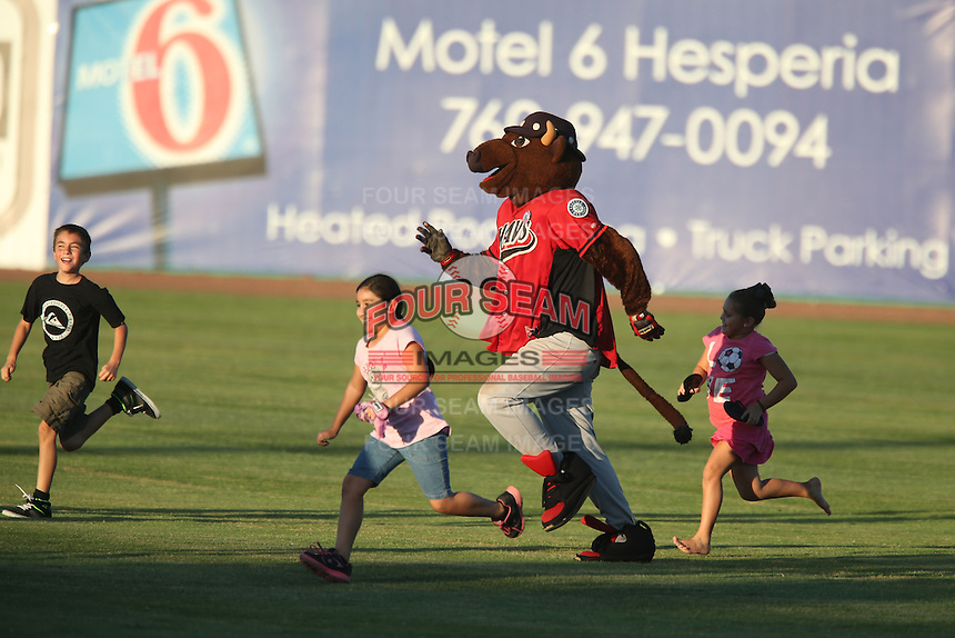 High Desert Mavericks mascot Wooly Bully runs with kids across the outfield between innings of a game against the Modesto Nuts at Heritage Field on June 29, 2014 in Adelanto, California. High Desert defeated Modesto, 6-1. (Larry Goren/Four Seam Images)
