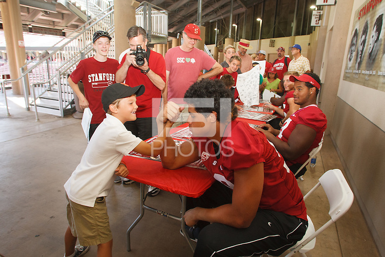 STANFORD,CA-- August 24, 2013:Luke Kaumatule arm wrestles a young fan during the 2013 Stanford Football Open House Saturday afternoon at Stanford Stadium.