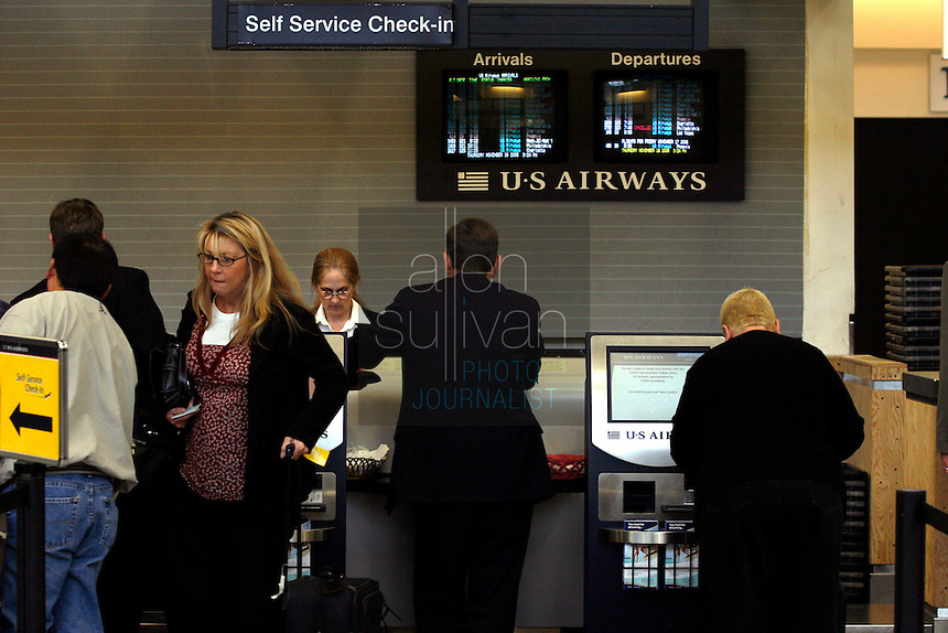 Passengers and workers at a US Airways check-in counter at Hartsfield-Jackson Atlanta International Airport. US Airways has made a bid to take over Delta Air Lines, which is headquartered in Atlanta.<br />
