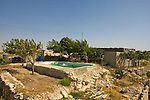 A Palestinian Swims in a pool overlooking the Palestinian town of Artas near Bethlehem on 02/06/2010. The pool is located close to the future site of Israel's controversial West Bank barrier & there is a demolition order from the Israeli Civil Administration Pending against it & the adjacent house.