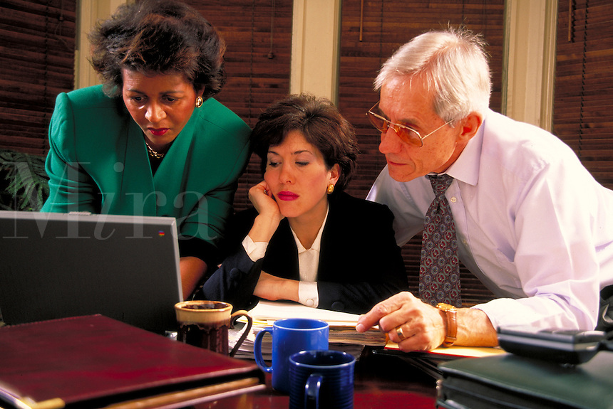 Three managers, a caucasian female, an African-American woman and a mature male work over coffee cups and laptop computer in conference room. Managers.