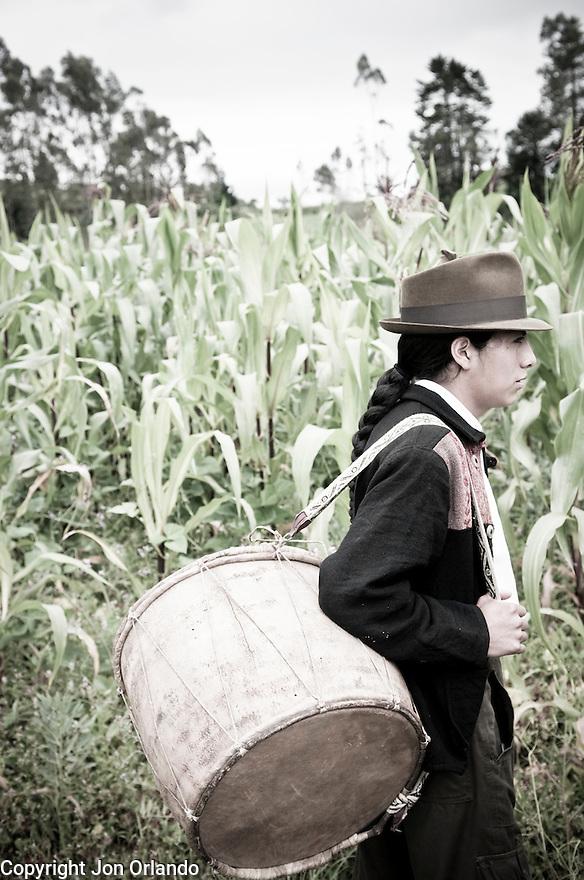 Rumiñahui Santillán, A member of The Pakarinka Sisari Ancestral Wisdom Center near Otavalo, Ecuador, heads to the fields to harvest fava beans.  Music and dance is a large part of the harvest ritual.