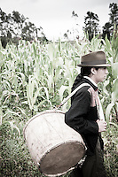 Rumiñahui Santillán, A member of The Pakarinka Sisari Ancestral Wisdom Center near Otavalo, Ecuador, heads to the fields to harvest fava beans.  Music and dance is a large part of the harvest ritual.