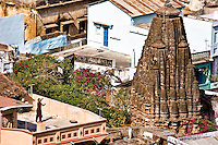 Girl flying  kite on roof of her house located near old temple in Rajasthan. (Photo by Matt Considine - Images of Asia Collection)