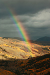 A rainbow, in autumn, arcs over the Ilium Valley near Telluride, Colorado, USA.  A rainbow shows a spectrum of light when sun shines through water drops in the air.
