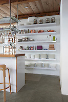 A series of floor-to-ceiling open shelves in the kitchen houses crockery and pots and pans