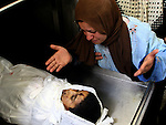 Palestinian woman look at her sun Wissam  Kafarne, eight  years old respectively, are seen in the morgue at the local hospital in the northern Gaza Strip town of Beit Hanun after being killed when a shell they were playing with detonated, 07 August 2007. The two Palestinian children were killed after an Israeli shell they were playing with exploded, witnesses and medics said. Eight other people, including children, were also wounded in the explosion. PHOTO BY: JINIPIX/ FADY ADWAN