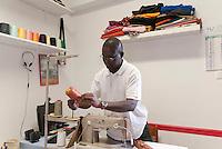 Il sarto senegalese Malick Niang nel suo laboratotio. Bagni pubblici di via Agliè. Torino