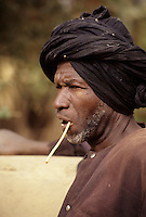 Near Niamey, Niger.  Fulani Farmer Ali Sambo Uses a Chewing Stick to Clean his Teeth.  A variety of soft, chewable woods is used to clean the teeth and remove plaque.