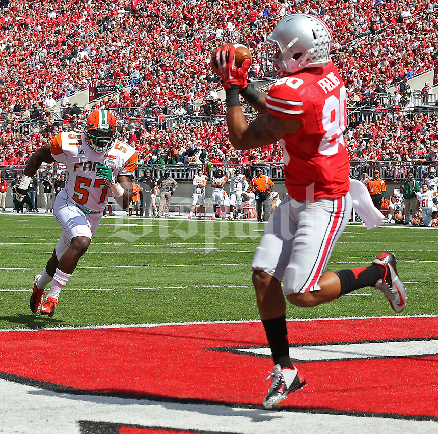 Ohio State Buckeyes wide receiver Chris Fields (80) catches a pass for a touchdown in the second quarter while Florida A&M Rattlers linebacker William Smalls (57) approaches in the second quarter of their NCAA football game at Ohio Stadium in Columbus, Ohio on September 21, 2013. (Columbus Dispatch photo by Brooke LaValley)