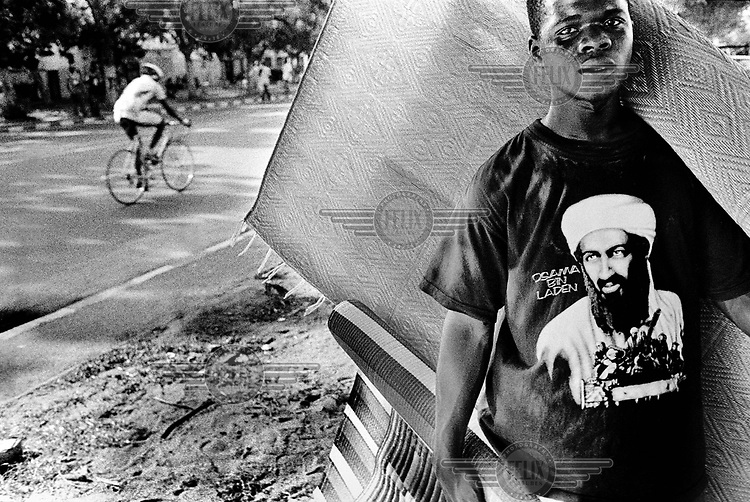 Carpet salesman, wearing an Osama Bin Laden T-shirt, beside the road where cyclists pass riding the prologue of the Tour du Senegal..The Tour du Senegal, a two-week cycle race held in average temperatures of 40 degrees Celsius, traverses the country with a total distance of 1168km.