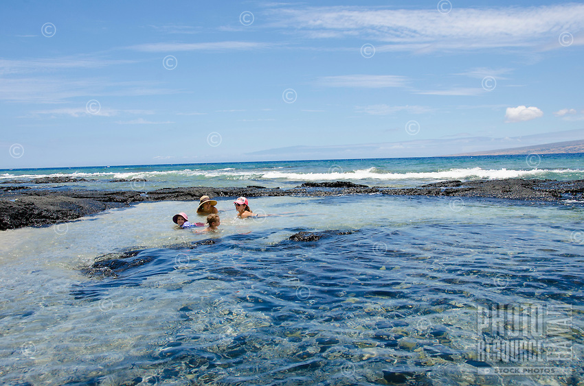 Two local families enjoy a sunny day floating and talking in tide pools at a beach in Puako, South Kohala, Hawai'i Island.