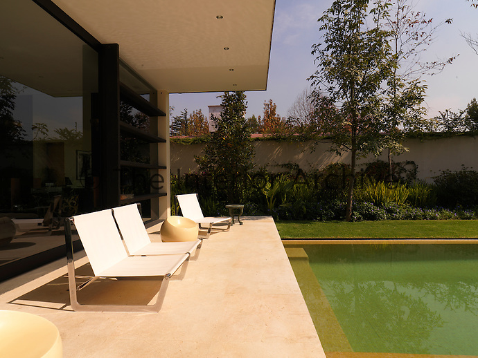 The terrace beyond the living room is cantelevered over the pool and furnished with a modern bench and chairs