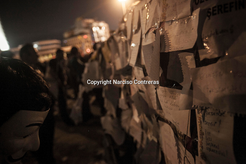 A protester reads the messages hung up on a destroyed vehicle in Gezi park given to the general public during a masive rally against the turkish government in Istanbul, Turkey.