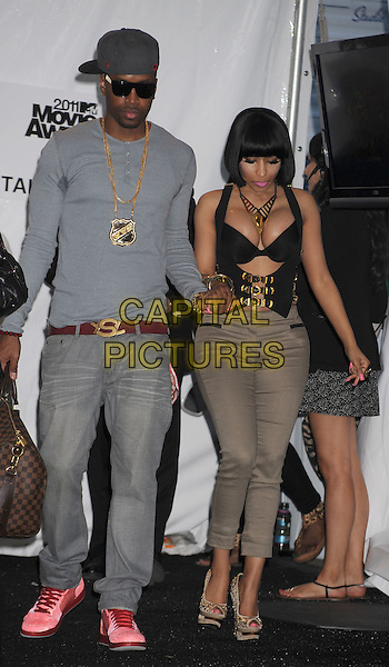 Scaff Beezy, Nicki Minaj.in the Press Room at the 2011 MTV Movie Awards at Universal Studios' Gibson Amphitheatre in Universal City, California, USA, June 5th 2011.  .pressroom full length bra cut out bustier  necklace black tattoo  buckles top gold grey gray khaki trousers cap hat  jeans  holding hands .CAP/ROT/TM.©TM/Roth Stock/Capital Pictures
