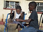 Hailey Kushaya (left) plays cards with his friend Tinashe Tangaiso in Harare, Zimbabwe. The 9-year old Kushaya has cerebral palsy and has lived with his grandmother since his parents died. At his school he uses an appropriately-designed and fitted wheelchair provided by the Jairos Jiri Association with support from CBM-US.