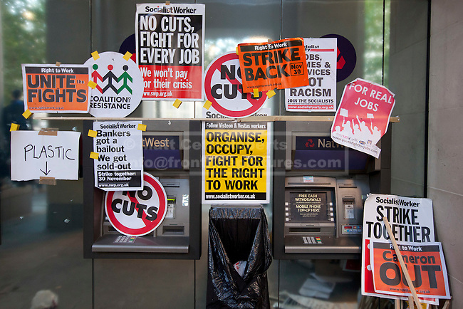 15/10/2011. LONDON, UK. Posters, stickers and placards are seen on a Natwest cashpoint in the square outside St Paul's Cathedral. Hundreds of demonstrators took to the streets as part of the Occupy London protest against the banks' handling of the financial crisis. As part of an anti-capitalist protest taking place in cities across the globe, demonstrators attempt to occupy Paternoster Square in London under the name Occupy London Stock Exchange.  After being refused entry to the square itself thousands of protesters occupied the area outside St Paul's Cathedral with some erecting tents. Credit should read: Matt Cetti-Roberts