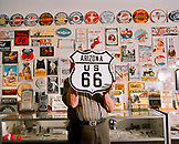 "USA, Arizona, man holding sign ""Arizona US 66"" in a sign store, Holbrook"