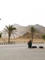 In the Sinai Peninsula, this woman and her two children wait for their transportation in a main road in the Sinai Peninsula. Sinai Peninsula, Egypt. Year: 2009.