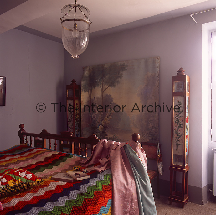 A blue bedroom with an artwork flanked by two decorated units. A glass pendant light hangs above a wooden double bed has a multi-coloured knitted cover.