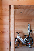 An electric bicycle and a pair of skis are propped against the wood clad walls of the entrance hall