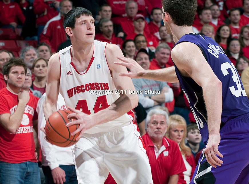 Wisconsin Badgers center J.P. Gavinski (44) handles the ball against Northwestern Wildcats forward Davide Curletti (30) during a Big Ten Conference NCAA men's college basketball game at the Kohl Center on February 27, 2011 in Madison, Wisconsin. Wisconsin won 78-63. (Photo by David Stluka)