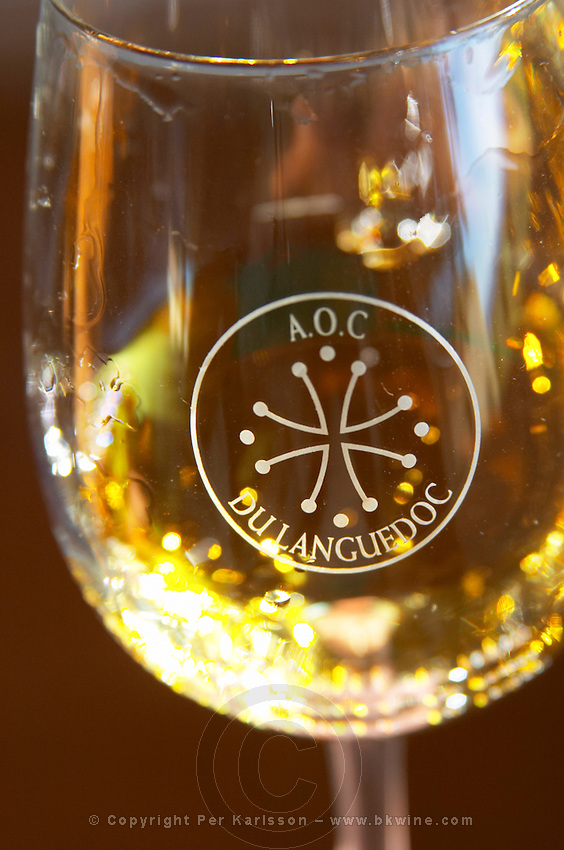 Glass embossed with AOC du Languedoc and the Languedocien Cathar cross. White wine. Chateau Rives-Blanques. Limoux. Languedoc. France. Europe.