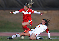 COLLEGE PARK, MARYLAND - April 03, 2013:  Stephanie Ochs (22) of The Washington Spirit loses the ball to a slide tackle from Erika Nelson (15) of the University of Maryland women's soccer team in a NWSL (National Women's Soccer League) pre season exhibition game at Ludwig Field in College Park Maryland on April 03. Maryland won 2-0.