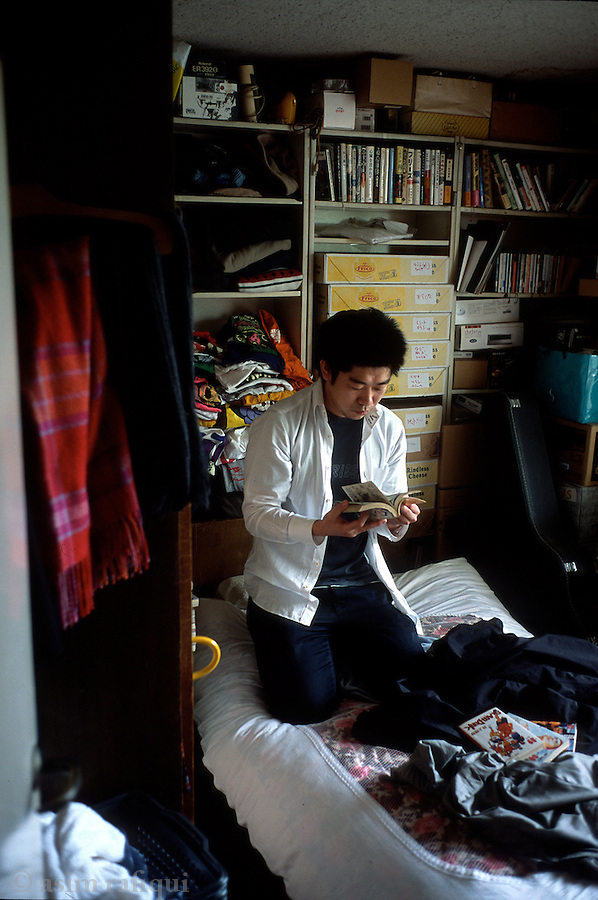 Takuma Horibe and avid manga comic fan pours over his collection in his room.