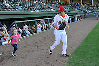 Center fielder Andrew Benintendi (2) of the Greenville Drive runs onto the field with a fan in a game against the Greensboro Grasshoppers on Wednesday, August 26, 2015, at Fluor Field at the West End in Greenville, South Carolina. Benintendi is a first-round pick of the Boston Red Sox in the 2015 First-Year Player Draft out of the University of Arkansas. Greenville won, 7-0. (Tom Priddy/Four Seam Images)