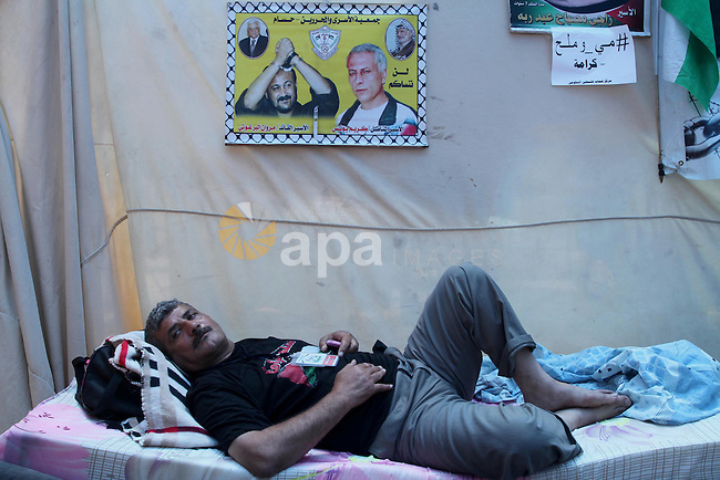 A Palestinian man on hunger strike stays at a tent in front of Red cross office in Gaza City, to solidarity with Palestinian prisoners, on May 31, 2014. It was about 120 Palestinians imprisoned without trial in Israel on an open hunger strike, and only salt intake, drinking water, for the past 30 days to demand an end to so-called 'administrative detention. Photo by Mohammed Asad