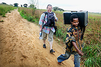 Ophthalmologist Dr Richard Hardi walks with a porter carrying medical equipment as they prepare to leave the remote village of Pania where he has been running a cataract clinic. <br /> From his base in Mbuji Mayi Hungarian ophthalmologist Friar Richard Hardi and his team travelled deep into the Congolese rainforest, by 4x4 and canoe, to treat people in isolated communities most of whom have never seen an ophthalmologist. At a small village called Pania they established a temporary field hospital and over the next three days made hundreds of consultations. Although both conditions are preventable, many of the patients they saw had Glaucoma or River Blindness (onchocerciasis) that had permanently damaged their eyesight. However, patients with cataracts, a clouding of the eye's lens, who were suitable for treatment were booked for an operation. For two days the team carried out the ten minute procedure on one patient after another. The surgery involves making a 2.2mm incision into the remove the damaged lens that is then replaced by an artificial one. Doctor Hardi is one of the few people willing to make such a journey but is inspired to do so by his faith and, as he says: 'Here I feel that I can really make a difference in people's lives'. /Felix Features