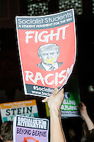 "A person holds a Socialist Students poster depicting Republican presidential nominee Donald Trump with tape over his mouth and the words ""Fight racism"" at a campaign rally for Green Party presidential nominee Jill Stein at Old South Church in Boston, Massachusetts, on Sun., Oct. 30, 2016."