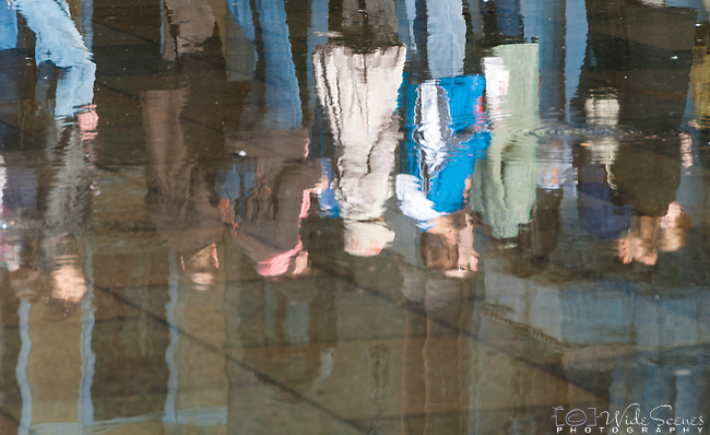 Reflection of People walking along the raised boardwalk in Piazza San Marco (St Mark's Square), Venice, Italy