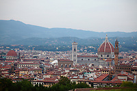 Firenze: A panoramic view with a part of the historical center in foreground. The photo is taken form the top of a hill nearby, and one can distinguish various landmarks of the town, among which dominate the ancient cathedral of Santa Maria del Fiore, and the ancient Palazzo Vecchio with its characteristic  tower (on the right), whereas one can see the main dome of the church of San Lorenzo, too (on the left).<br />