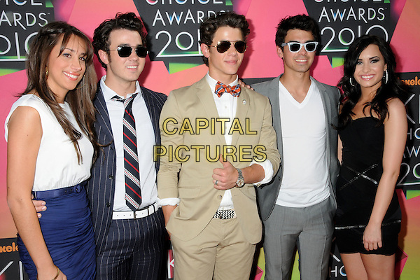 DANIELLE JONAS (nee DELEASA), KEVIN JONAS, JOE JONAS, DEMI LOVATO & NICK JONAS .at the 23rd Annual Nickelodeon Kids' Choice Awards 2010 held at Pauley Pavilion in Westwood, California, USA, March 27th 2010 .arrivals kids half length brothers wife husband couple family siblings sunglasses blue navy skirt white top t-shirt grey gray suit jacket jeans beige bow tie black dress strapless tie pinstripe red hand in pocket thumb up gesture ray bans  .CAP/ADM/BP.©Byron Purvis/Admedia/Capital Pictures