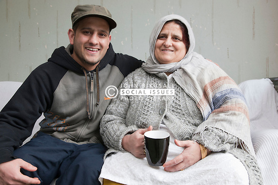 Portrait of South Asian woman and her son smiling to camera.