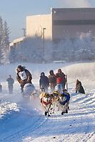 Musher William Pinkham mushes down the Chena River at the start of the 2008 Yukon Quest in Fairbanks, Alaska.