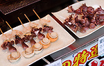Japanese street food, seafood skewers, grilled scallop Hotateyaki, baby octopus Takotamago and shrimp on a stick in Kyoto, Japan