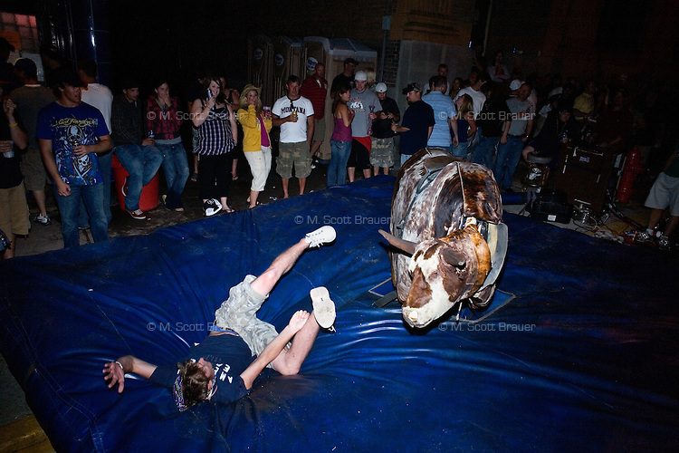 Revelers attempt to ride a mechanical bull late at night during the Evel Knievel Days festival in Butte, Montana, USA.