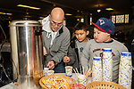 WATERBURY, CT. 21 December 2019-122119BS293 - From left, Eddie Martinez of Waterbury helps his two kids Ely, 8, and Edgardo, 6, get some hot chocolate, during a Christmas Party for the less fortunate and homeless at the Basilica of Immaculate Conception in Waterbury on Saturday. Bill Shettle Republican-American