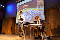 The Boring Conference at Conway Hall. Jason Ward does a puzzle on stage while James Ward, organiser of the conference, talks to the audience about the Boring Conference. The Boring Conference is a one-day celebration of the mundane, the ordinary, the obvious and the overlooked; subjects often considered trivial and pointless, but when examined more closely reveal themselves to be deeply fascinating.<br /> <br /> It was created in response to the cancellation of the 2010 Interesting Conference. It seemed like the obvious thing to do.