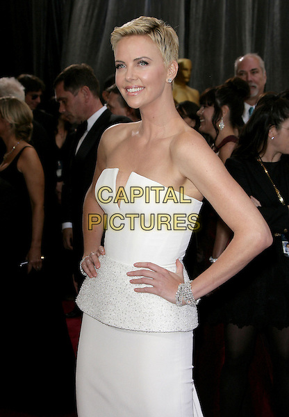 Charlize Theron (wearing Dior Couture).85th Annual Academy Awards held at the Dolby Theatre at Hollywood & Highland Center, Hollywood, California, USA..February 24th, 2013.oscars half length dress white strapless peplum short cropped hair pixie cut hands on hips bracelets  .CAP/ADM.©AdMedia/Capital Pictures.